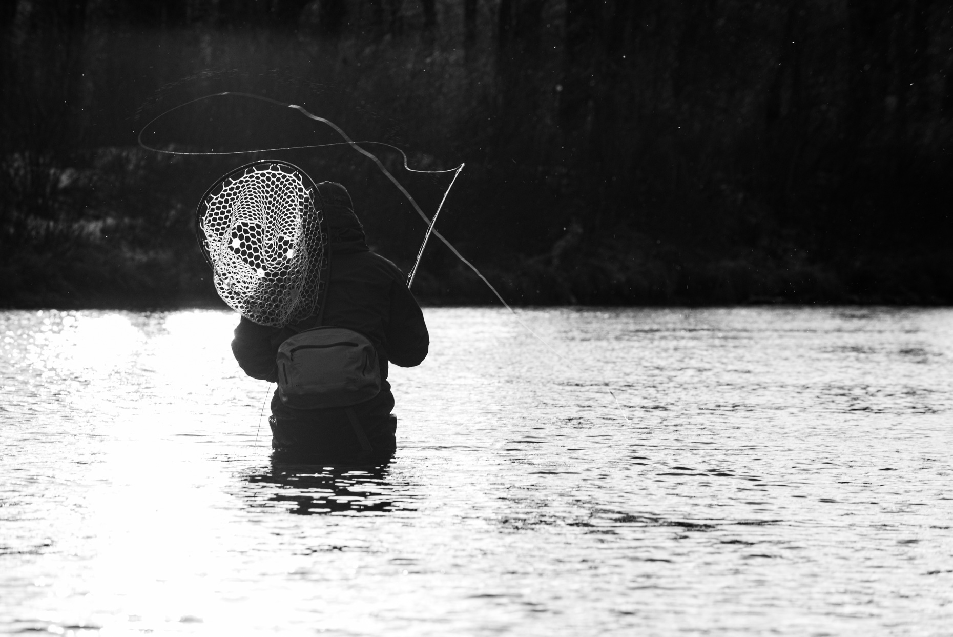 a fly fisherman casting on a cloudy day in New Hampshire